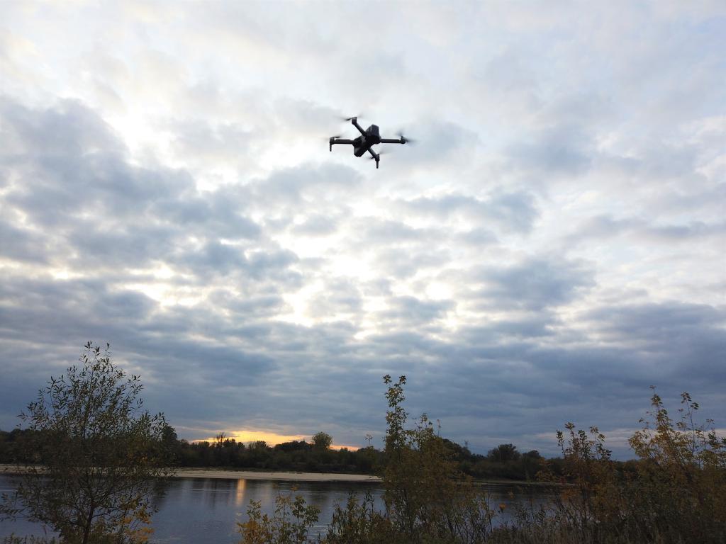 Recenzja drona SJRC F11 PRO - dron odlatuje w kierunku zachodu słońca